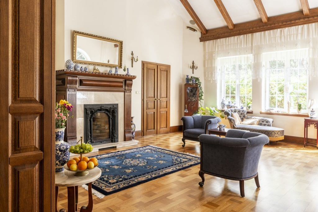 Blue armchairs and patterned carpet in front of wooden fireplace